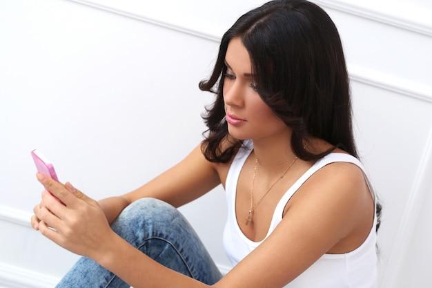 Attraktiver brunette, der auf dem boden sitzt Kostenlose Fotos