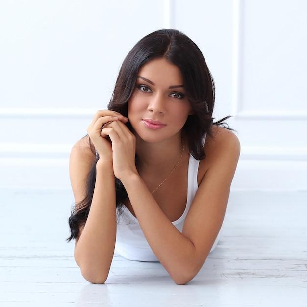 Attraktiver brunette, der auf den boden legt Kostenlose Fotos