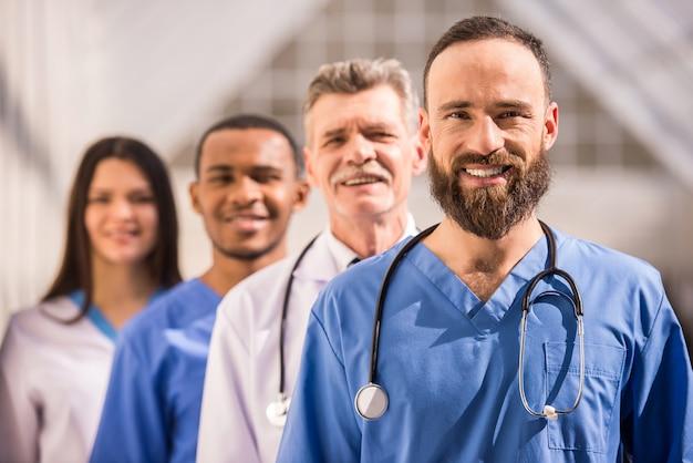 Attraktiver doktor vor medizinischer gruppe im krankenhaus. Premium Fotos