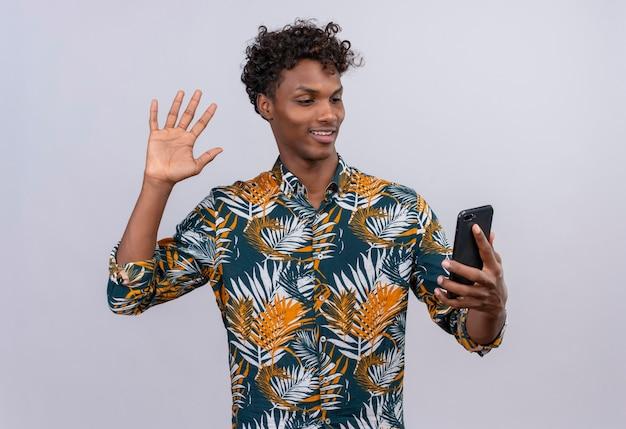 Attraktiver gut aussehender dunkelhäutiger mann mit dem lockigen haar im bedruckten blatthemd, das mit freund während des videoanrufs spricht und hand auf frontkamera des mobiltelefons winkt Kostenlose Fotos