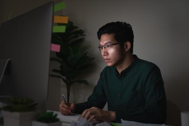Attraktiver junger asiatischer mann, der auf der schreibtischtabelle betrachtet laptop-computer in der dunklen späten nacht sitzt Premium Fotos