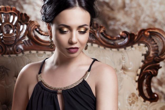 Attraktiver junger brunette, der auf schönem sofa, porträtnahaufnahme, goldaugenschminke sitzt Premium Fotos