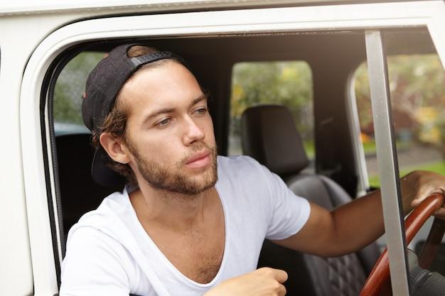 Attraktiver junger kaukasischer hipster-mann mit bart, der schwarze baseballkappe und weißes v-ausschnitthemd trägt, das weißes sport utility vehicle entlang der landstraße fährt Kostenlose Fotos