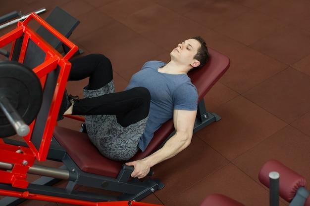 Attraktiver junger mann, der beinpresse auf maschine im fitnessstudio tut Premium Fotos