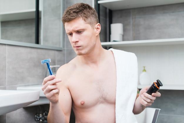 Attraktiver junger mann, der das blaue rasiermesser hält einen elektrischen trimmer im badezimmer betrachtet Kostenlose Fotos