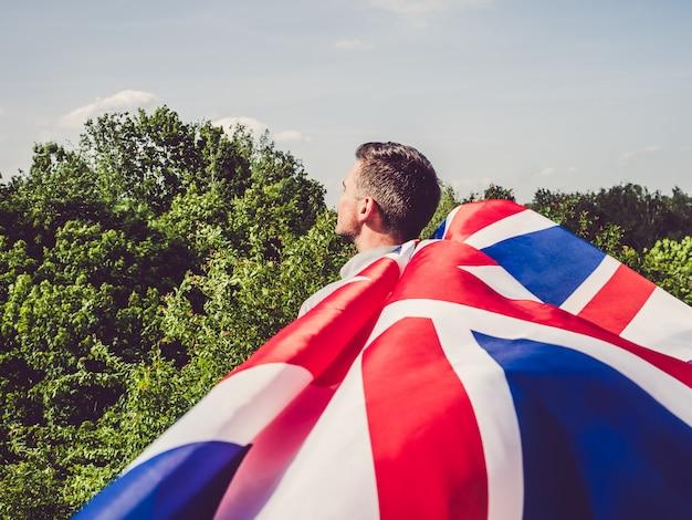 Attraktiver, junger mann, der eine britische flagge wellenartig bewegt Premium Fotos