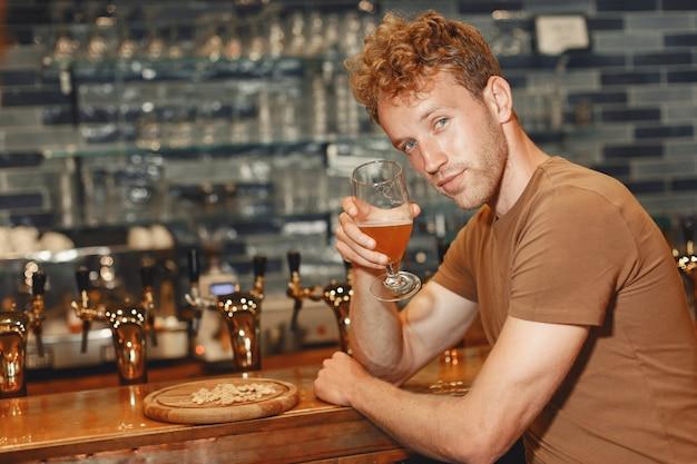Attraktiver junger mann, der hinter der bar steht. mann in einem braunen t-shirt hält ein glas in seinen händen. Kostenlose Fotos