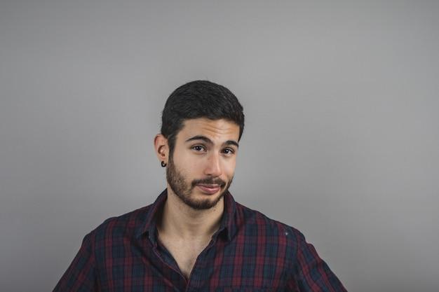 Attraktiver junger mann mit dem bart, der geradeaus, junger mann glücklich schaut Premium Fotos
