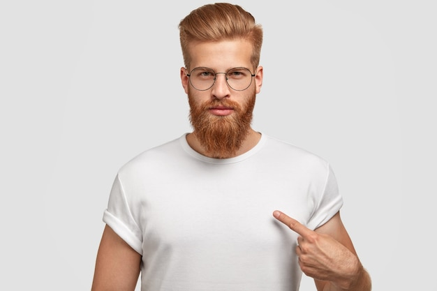 Attraktiver junger mann mit rotem haarschnitt und bart, zeigt auf leeres t-shirt Kostenlose Fotos