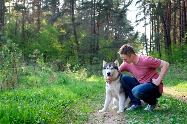 Attraktiver junger mann mit seinem hundemalamute auf einem weg im wald Premium Fotos