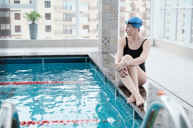 Attraktiver junger weiblicher schwimmer in der blauen kappe, die am rand des pools sitzt und wasser im pool betrachtet Premium Fotos