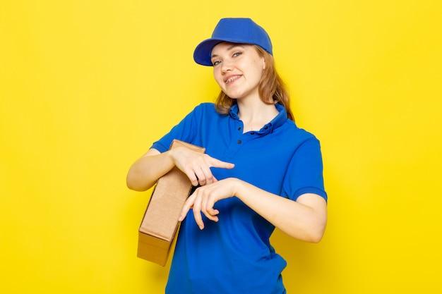 Attraktiver kurier der weiblichen vorderansicht in der blauen kappe des blauen poloshirts und in der jeans, die paket hält, das ihr handgelenk berührt, das auf dem gelben hintergrundlebensmittelservicejob lächelt Kostenlose Fotos