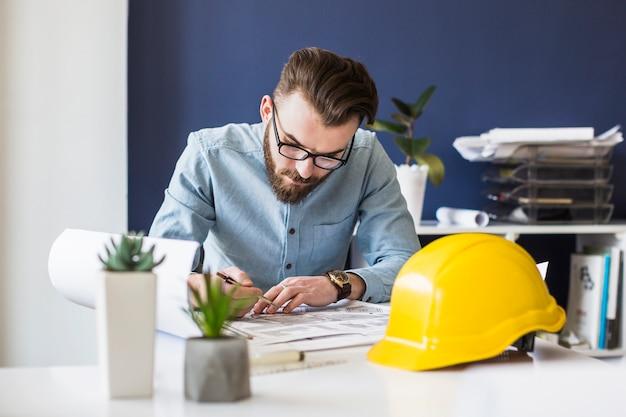 Attraktiver männlicher ingenieurzeichnungsplan auf plan am arbeitsplatz Kostenlose Fotos