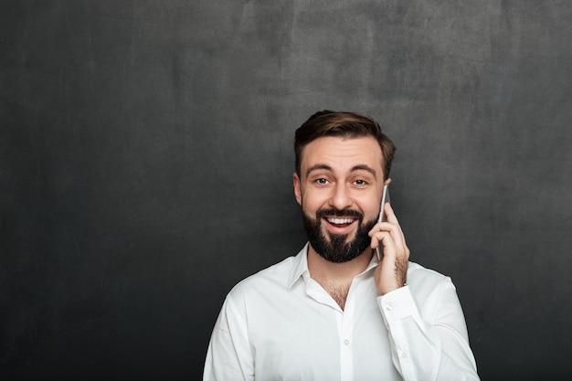 Attraktiver mann, der auf dem smartphone hat das angenehme gespräch schaut auf kamera über graphitkopienraum spricht Kostenlose Fotos