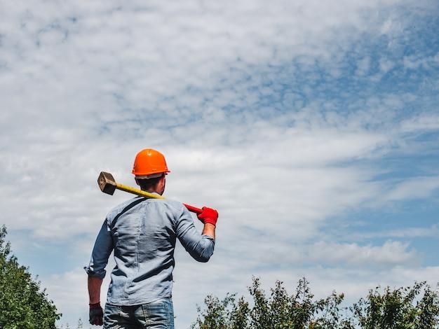 Attraktiver mann, der einen hammer im park hält Premium Fotos
