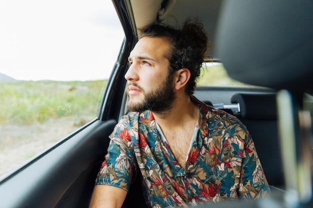 Attraktiver mann, der oben autofenster betrachtet Kostenlose Fotos