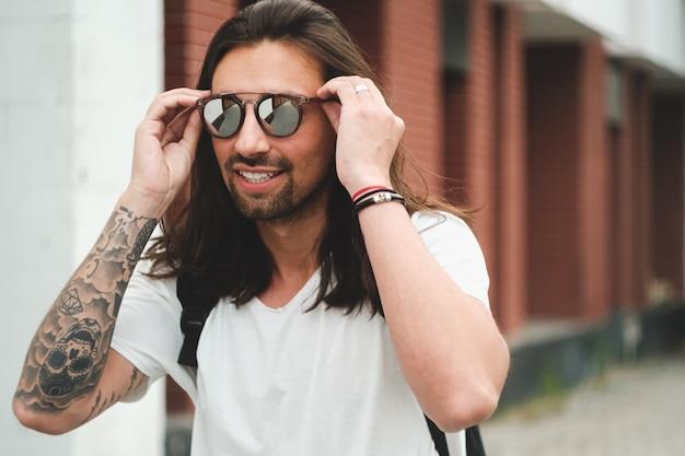 Attraktiver mann des porträts mit sonnenbrille auf dem städtischen szenenlächeln Kostenlose Fotos