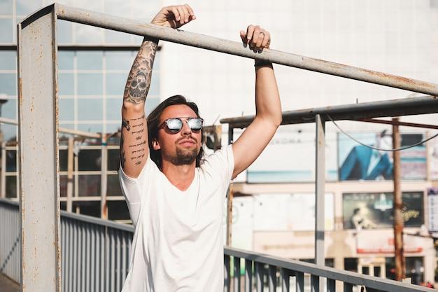 Attraktiver mann mit der sonnenbrille, die heraus in der stadt hängt Kostenlose Fotos