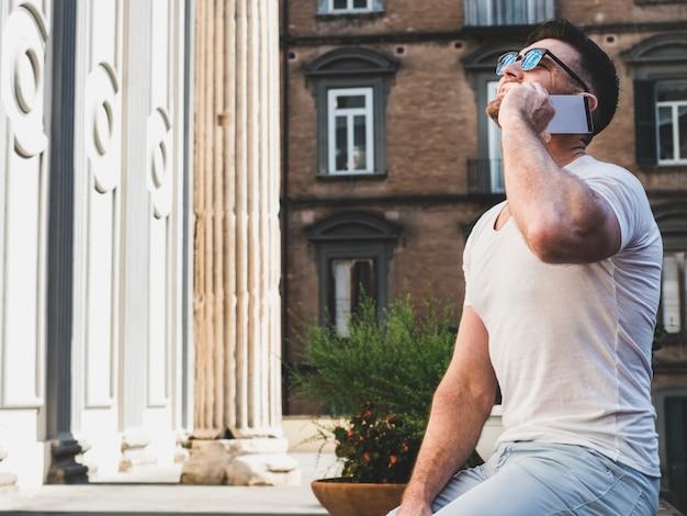 Attraktiver mann mit einem telefon auf dem hintergrund von hellem Premium Fotos