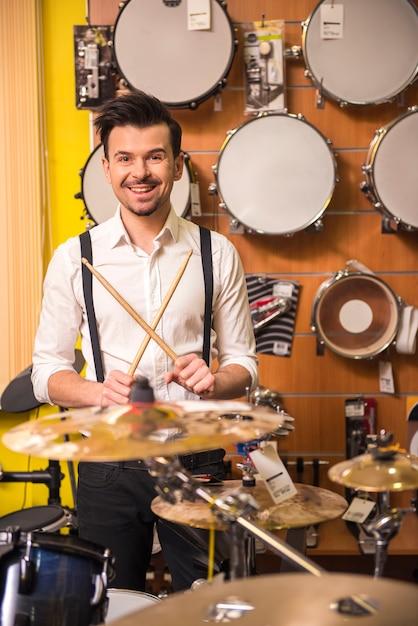 Attraktiver mann spielt schlagzeug im musikladen. Premium Fotos