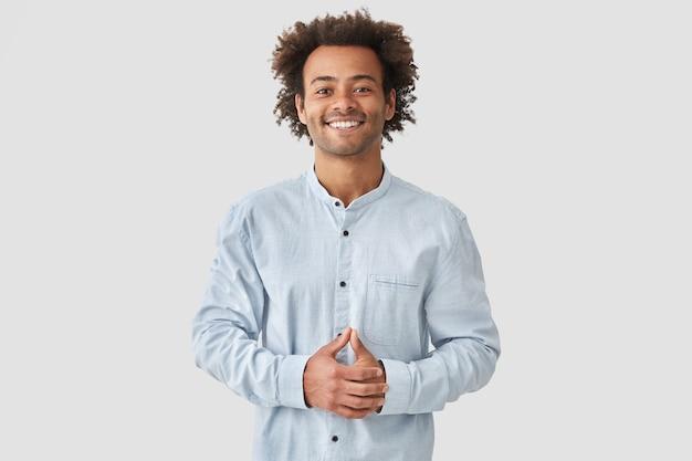 Attraktiver mischling mit positivem lächeln, zeigt weiße zähne, hält die hände auf dem bauch, ist in hochstimmung, trägt ein weißes hemd und freut sich über positive momente im leben. menschen- und emotionskonzept Kostenlose Fotos