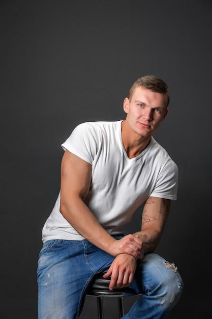 Attraktiver modemann, der die kamera beim sitzen auf einem stuhl betrachtet. Premium Fotos