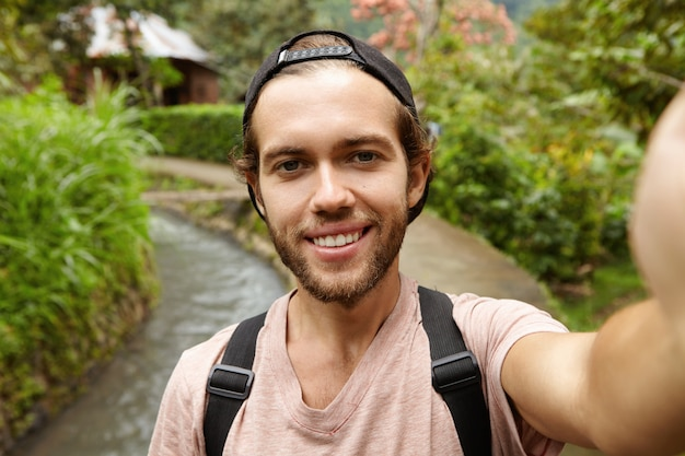 Attraktiver modischer reisender mit bart, der rucksack trägt, der selfie nimmt und auf landstraße aufwirft. reisen, abenteuer Kostenlose Fotos