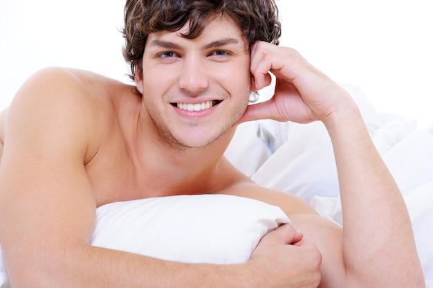 Attraktiver sexy lächelnder junger nackter mann, der im bett mit kissen liegt Kostenlose Fotos