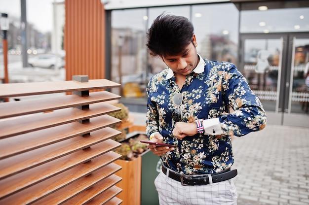 Attraktiver und gutaussehender stilvoller mann tragen auf hemd, hält handy, schaut auf uhren und steht auf der terrasse des modernen lounge-cafés während seiner arbeitspause Premium Fotos