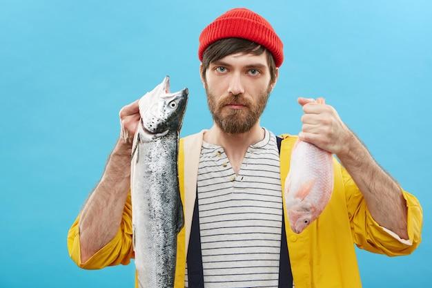 Attraktiver unrasierter junger männlicher fischhändler, der nach dem hochseefischen zwei fische in den händen hält und ihnen anbietet, frische produkte zu kaufen. fischhandel und marketing. hobby-, sport- und erholungskonzept Kostenlose Fotos