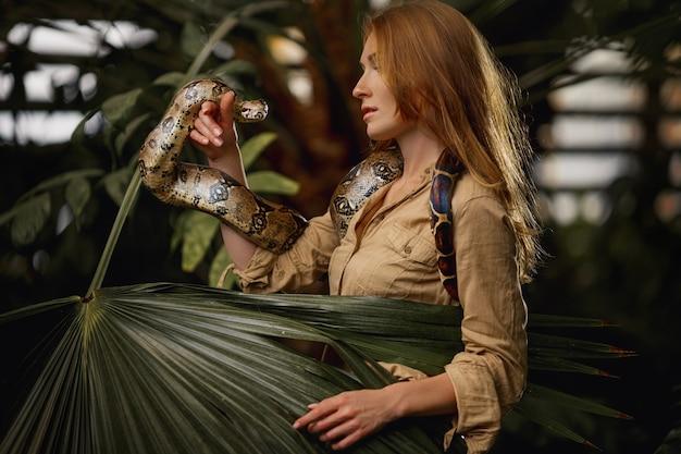 Attraktiver weiblicher tierpfleger mit pythonschlange in tropischer natur Premium Fotos