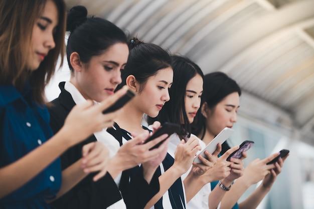 Attraktives asiatisches geschäftsfrauteam, das smartphone spielt Premium Fotos