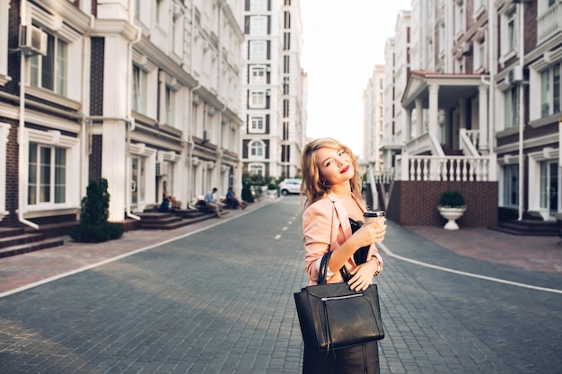 Attraktives blondes mädchen mit weinigen lippen, die mit tasse kaffee in der korallenjacke auf straße gehen. sie trägt eine schwarze tasche Kostenlose Fotos