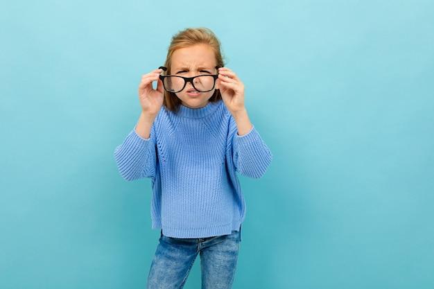 Attraktives europäisches mädchen schaut durch brille auf hellblauer wand Premium Fotos