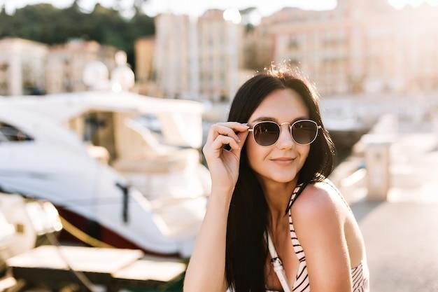 Attraktives fröhliches mädchen mit bronzehaut, das schwarze sonnenbrille hält und draußen mit booten ruht Kostenlose Fotos