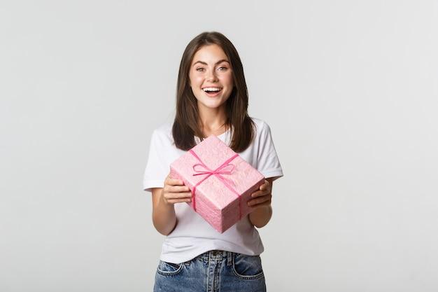 Attraktives glückliches brünettes mädchen, das geburtstagsgeschenk hält und fröhlich lächelt. Kostenlose Fotos