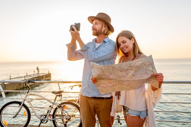 Attraktives glückliches paar, das im sommer auf fahrrädern, mann und frau mit blondem haar im boho-hipster-stil unterwegs ist und spaß zusammen hat Kostenlose Fotos