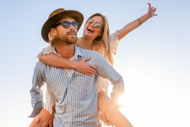 Attraktives glückliches paar, das lachend im sommer auf dem seeweg lacht, mann und frau, die sonnenbrille tragen Kostenlose Fotos