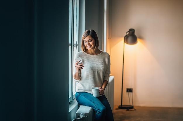 Attraktives junges mädchen, das telefon beim sitzen nahe fenster verwendet. Premium Fotos