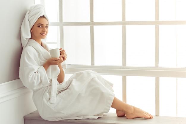 Attraktives junges mädchen im bademantel und mit einem tuch. Premium Fotos