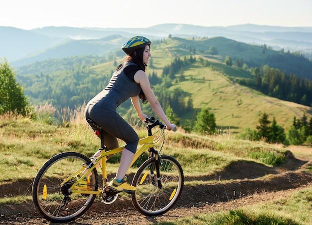 Attraktives lächelndes frauenradfahrerreiten auf gelbem fahrrad auf ländlicher spur in den bergen, tragender sturzhelm, am sommertag. Premium Fotos
