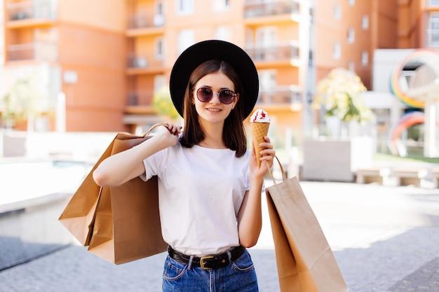 Attraktives mädchen, das mit eiscreme geht, das einkaufstaschen im einkaufszentrum hält Kostenlose Fotos
