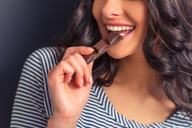 Attraktives mädchen, das schokolade und das lächeln isst. Premium Fotos