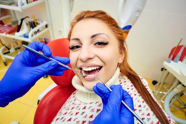 Attraktives mädchen im roten zahnmedizinischen stuhl an der aufnahme von zahnärzten Premium Fotos