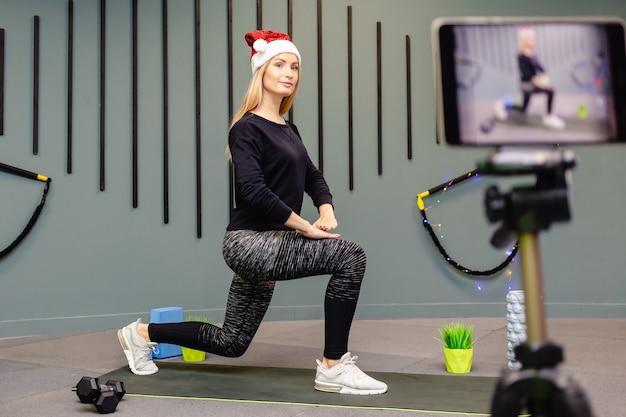 Attraktives mädchen in der weihnachtsmütze macht fitnessübungen und zeichnet sich vor der kamera auf. Premium Fotos