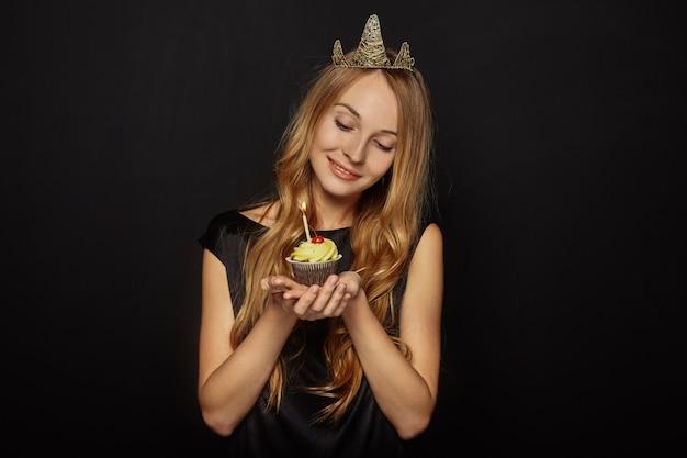 Attraktives mädchen mit einer krone und einem kleinen kuchen Kostenlose Fotos