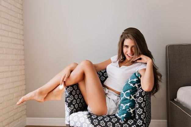 Attraktives mädchen mit langen haaren in hemden im stuhl in der modernen wohnung. sie berührte die beine und lächelte. Kostenlose Fotos