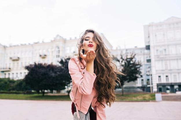 Attraktives mädchen mit langer frisur, die spaß in der stadt hat. sie hat eine rosa jacke und sendet einen kuss mit weinigen lippen. Kostenlose Fotos