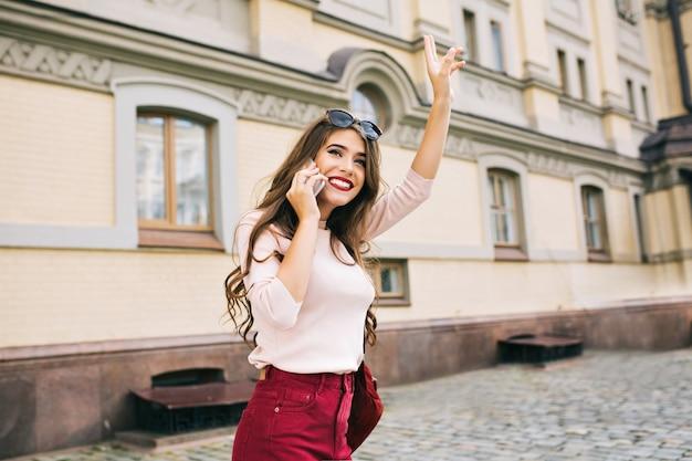 Attraktives mädchen mit langer frisur geht in der stadt spazieren. sie telefoniert und gratuliert jemandem. Kostenlose Fotos
