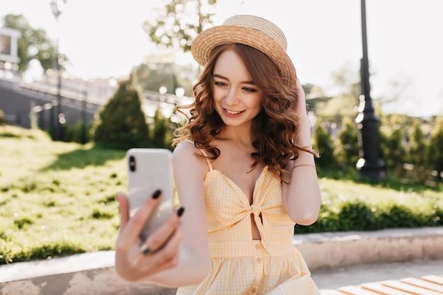 Attraktives mädchen mit lockiger frisur, die selfie im park macht. hübsche junge frau des ingwers, die foto von sich macht, während sie draußen ruht. Kostenlose Fotos